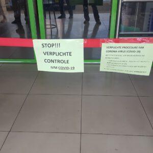 Waarschuwing geschreven op papier bij de ingang van een supermarkt.