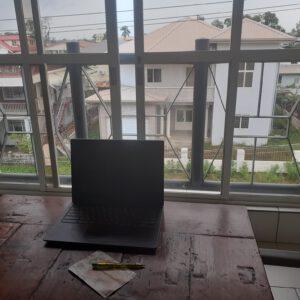 Een laptop op een tafel voor een groot raam.